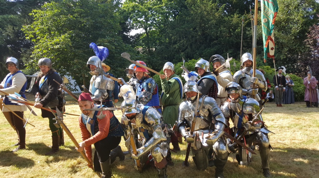 Beaufort Companye in full medieval armour with their weapons pointed towards the camera