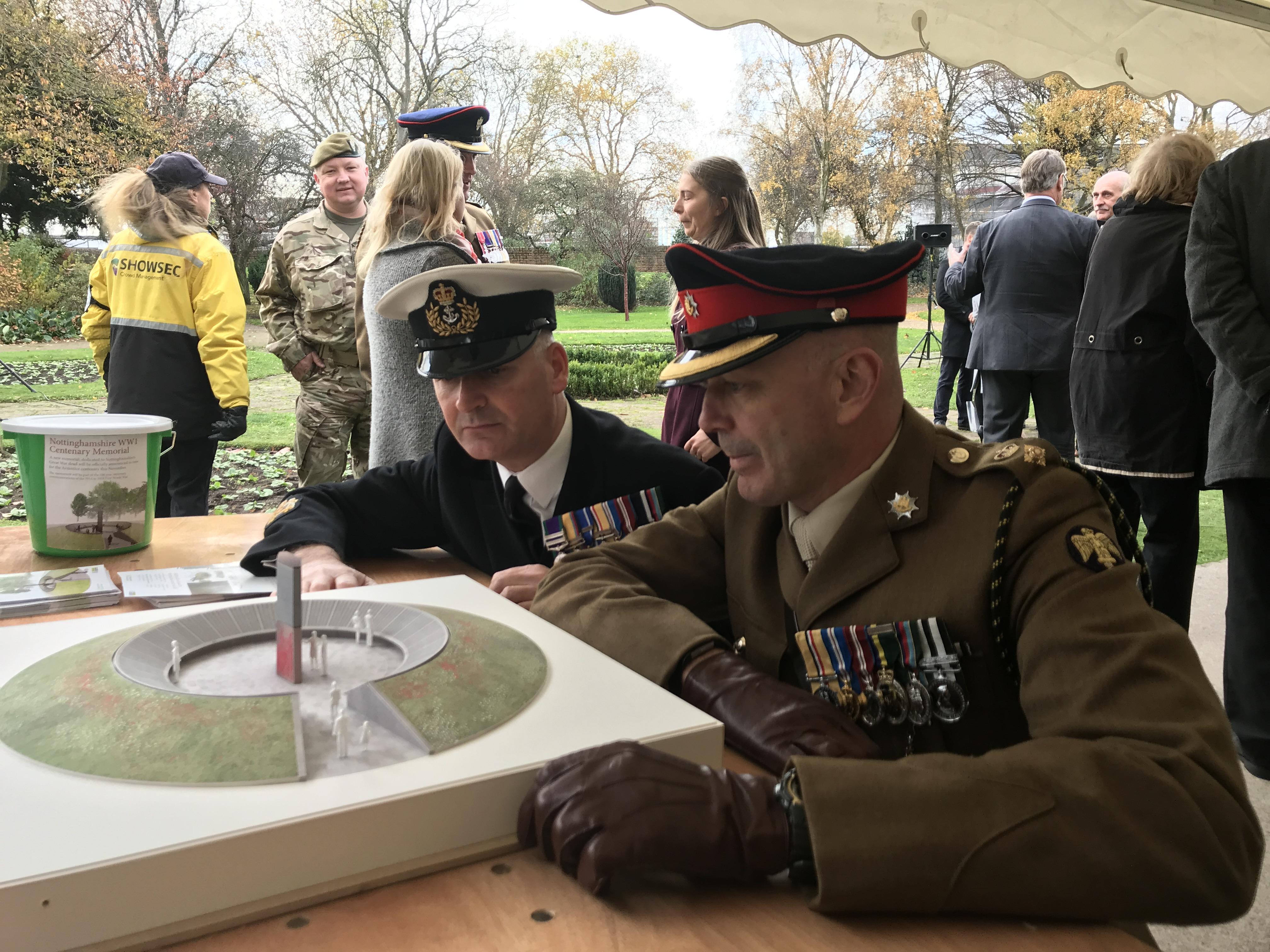 Two uniformed officers look at a model of the new memorial
