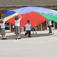 Primary school children playing with parachute on school playground